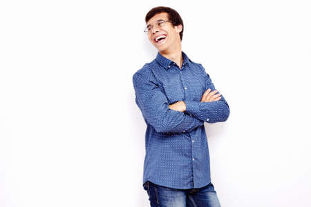 laughing out loud: Young hispanic man wearing blue shirt and glasses standing with crossed arms on his chest and laughing out loud against white wall - humor concept
