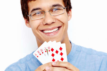 royal flush: Close up portrait of young hispanic man wearing jeans shirt and glasses holding Royal Flush (highest-ranking standard poker hand) in his hand and smiling against white wall - gambling winnings concept