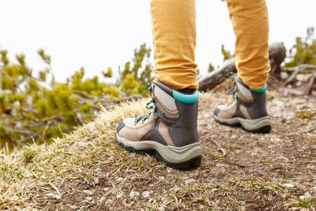 conquers: Back view close up of woman wearing yellow pants and hiking boots outdoors - adventure concept