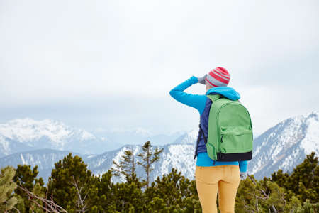 conquers: Back view of young woman wearing pink hat, blue jacket, green backpack, yellow pants and hiking boots standing against winter mountain valley and looking far covering her eyes by hand - adventure concept