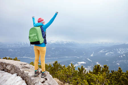 conquers: Back view of young woman wearing pink hat, blue jacket, green backpack, yellow pants and hiking boots raising her hands against winter mountain valley celebrating successful climb - goal concept