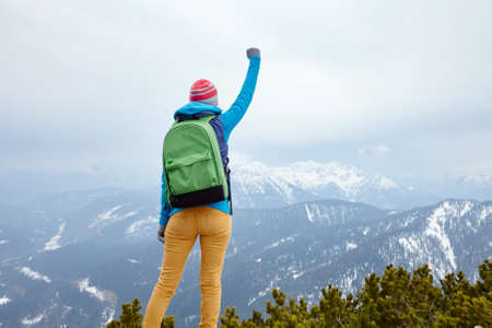 conquers: Back view of young woman wearing pink hat, blue jacket, green backpack and yellow pants raising her hand against winter mountains celebrating successful climb - goal concept Stock Photo