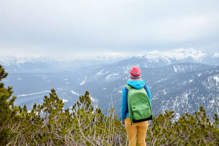 conquers: Back view of young woman wearing pink hat, blue jacket, green backpack and yellow pants standing against winter mountain valley - adventure concept Stock Photo