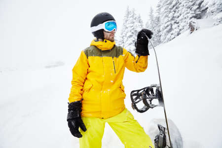 snowboard: Close up portrait of male snowboarder wearing helmet with glasses, yellow jacket and pants, black gloves standing with snowboard in one hand and planning freeride route against blizzard - extreme sports concept