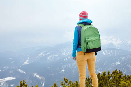 conquers: Back view of young woman wearing pink hat, blue jacket, green backpack and yellow pants standing against winter mountains - adventure concept Stock Photo