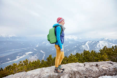 hiking: Side view of young woman wearing pink hat, blue jacket, green backpack, yellow pants and hiking boots standing against winter mountain valley - adventure concept
