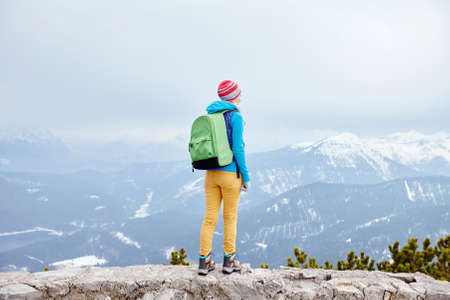 conquers: Back view of young woman wearing pink hat, blue jacket, green backpack, yellow pants and hiking boots standing against winter mountain valley - adventure concept