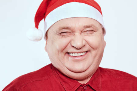 laughing out loud: Close up portrait of laughing out loud aged man wearing Santa Claus hat and red shirt against white background - Christmas concept