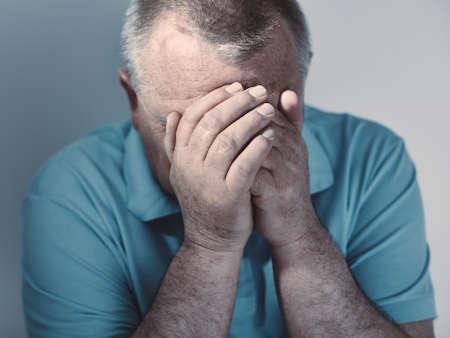 Dramatic cool toned close up portrait of aged man sitting with hands on his face against white wall - depression concept Stock Photo