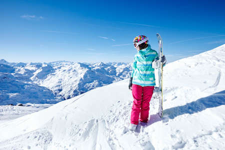 snowboard: Female snowboarder wearing colorful helmet, blue jacket, grey gloves and pink pants standing with snowboard in one hand and looking at beautiful alpine mountain landscape - winter sports concept Stock Photo