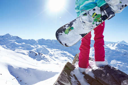 snowboard: Back view close up of female snowboarder wearing colorful helmet, blue jacket, grey gloves and pink pants standing with snowboard in one hand and enjoying sunny alpine mountain landscape - winter sports concept