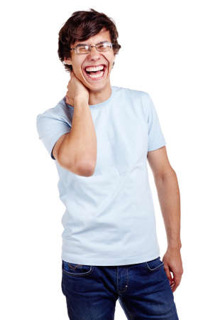 laughing out loud: Portrait of young hispanic man wearing glasses, blue t-shirt and jeans standing with hand behind his neck and loudly laughing isolated on white background - laughter concept
