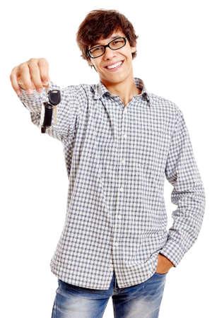 Jonge Spaanse man met geruit shirt, blauwe spijkerbroek en zwarte bril standhouden autosleutels en lachend op een witte achtergrond - nieuwe drivers-concept