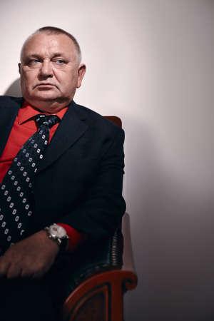malandros: Hombre de negocios serio mediana edad llevaba traje negro, camisa roja y el reloj de pulsera se sienta en el sof� estilo antiguo en el cargo y mira a un lado