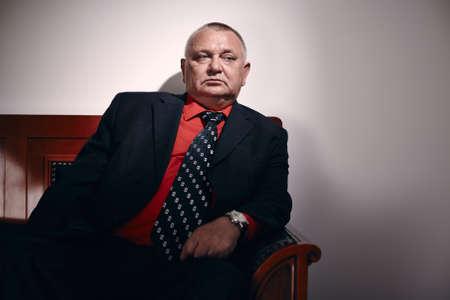 malandros: Hombre de negocios serio mediana edad llevaba traje negro, camisa roja y el reloj de pulsera se sienta en el sofá estilo antiguo en el cargo y mira a un lado