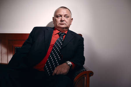 malandros: Serious middle aged businessman wearing black suit, red shirt and wristwatch sitting on old fashioned sofa in office and looking aside