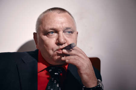 malandros: Close up portrait of serious middle aged businessman wearing black suit and red shirt smoking cigar in office