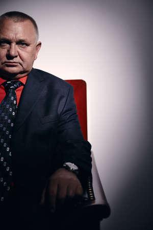 malandros: Retrato de graves negocios de mediana edad el uso de traje negro, camisa roja y el reloj de pulsera se sienta en el sof� estilo antiguo en el cargo