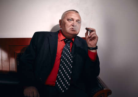 malandros: Serious middle aged businessman wearing black suit, red shirt and wristwatch sitting on old fashioned sofa in office and smoking cigar
