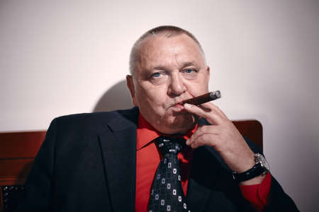 Portrait of serious middle aged businessman wearing black suit, red shirt and wristwatch sitting on old fashioned sofa in office and smoking cigar Stockfoto
