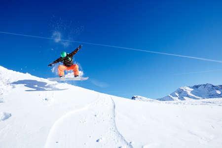 Male snowboarder wearing green helmet, black jacket and orange pants having fun jumping against blue sky on ski resort piste - winter sports concept