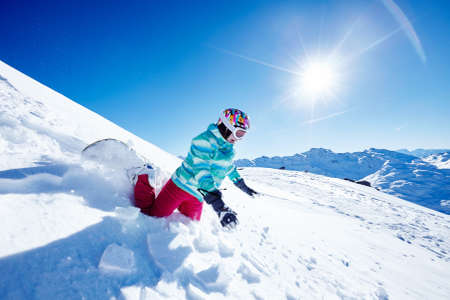 Female snowboarder wearing colorful helmet, blue jacket, grey gloves and pink pants falling off on her knees and wrists on ski resort piste - winter sports fail concept. Focus in motion Stock Photo