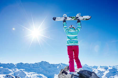 snowboard: Back view of female snowboarder wearing colorful helmet, blue jacket, grey gloves and pink pants standing with snowboard raised in her hands overhead and enjoying sunny alpine mountain landscape - winter sports concept