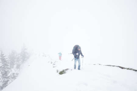 conquers: Male and female mountain climbers with huge backpacks and trekking poles having hard hiking trip during winter storm in Austrian Alps