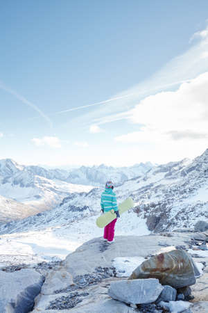 snowboard: Back view of female snowboarder wearing colorful helmet, blue jacket, grey gloves and pink pants standing with snowboard in one hand and enjoying alpine mountain landscape - winter sports concept Stock Photo