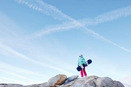 snowboard: Back view of female snowboarder wearing colorful helmet, blue jacket, grey gloves and pink pants standing on rocks with snowboard in one hand against X sign on sky - winter sports concept
