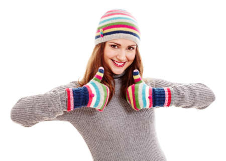 Young beautiful woman wearing warm autumn clothes - colorful hat and mittens, grey sweater - showing thumb up hand gesture with both hands and smiling isolated on white background - say no to cold and flu