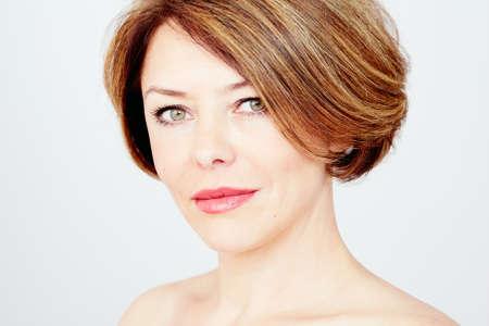 Close-up portret van mooie vrouw van middelbare leeftijd met kort bruin haar, rode lippen en frisse make-over witte achtergrond - schoonheid concept Stockfoto