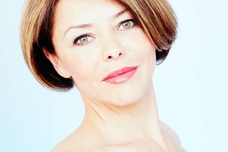 mujer desnuda: Close up retrato de la hermosa mujer de mediana edad con el pelo castaño y corto, los labios rojos y el maquillaje fresco sobre fondo azul - concepto de belleza Foto de archivo