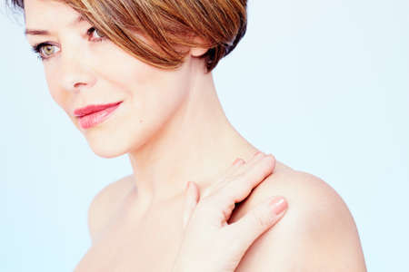 Close up portrait of beautiful middle aged woman with short brown hair, red lips and fresh makeup standing with hand on her shoulder and looking aside over blue background - beauty concept Stock Photo