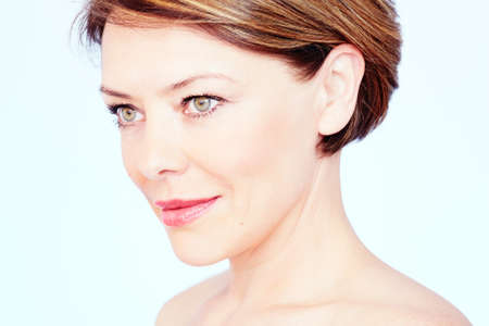 Close up portrait of beautiful middle aged woman with short brown hair, red lips and fresh makeup looking aside over blue background - beauty concept Stock Photo