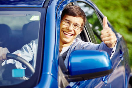 drivers: Young happy hispanic man wearing glasses sitting inside car, holding steering wheel,  showing thumb up hand gesture through car window and laughing - new drivers concept