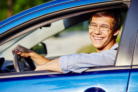 drivers: Young happy hispanic man wearing glasses and blue jeans shirt sitting behind wheel of his car and smiling through window - new drivers concept Stock Photo