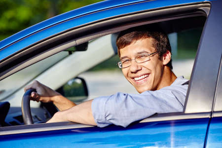 drivers license: Young happy hispanic man wearing glasses and blue jeans shirt sitting behind wheel of his car and smiling through window - new drivers concept Stock Photo