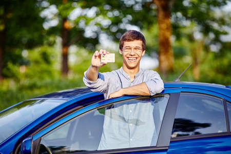 drivers: Young hispanic man wearing glasses and jeans shirt holding out his driving license and laughing against blue car outdoors - new drivers concept