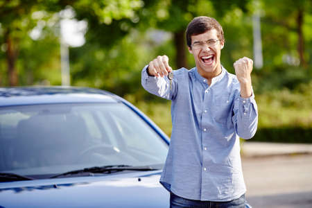 drivers: Young happy hispanic man wearing glasses holding out car keys and celebrating win with raised fist and scream against blue car outdoors - new drivers concept Stock Photo