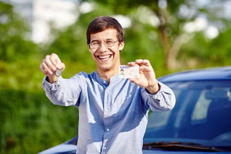 finger proof: Young hispanic man wearing glasses and blue jeans shirt holding in his hands car keys and driving license against car outdoors - new drivers concept