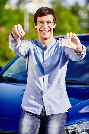 passed test: Young hispanic man wearing glasses and blue jeans shirt holding in his hands car keys and driving license against car outdoors - new drivers concept
