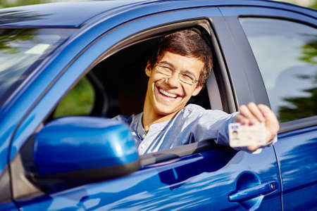 Young hispanic man wearing glasses and jeans shirt sitting behind wheel and holding out his driving license through car window - new drivers concept Standard-Bild