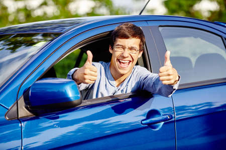 test passed: Close up of young happy hispanic man wearing glasses showing thumb up hand gesture with both hands and laughing through car window - new drivers concept Stock Photo