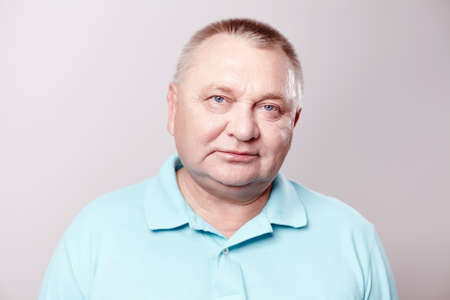 Portrait of aged man wearing blue shirt against white background - retirement concept