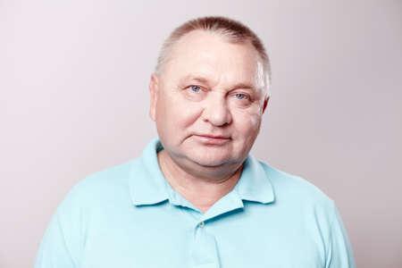 Portret van oude man draagt blauwe shirt tegen een witte achtergrond - concept van pensioen Stockfoto