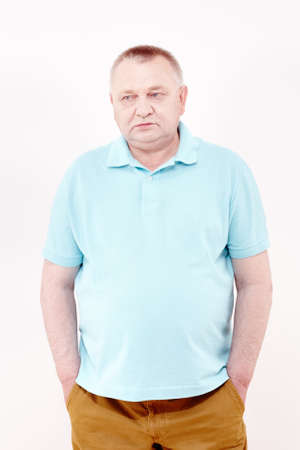 looking aside: Mature serious man wearing blue shirt and brown trousers standing with hands in pockets and looking aside against white wall - depression concept