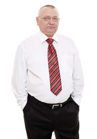 Serious middle aged businessman wearing glasses, red and black striped tie with white shirt and black trousers standing with hands in pockets isolated on white background - human resources concept