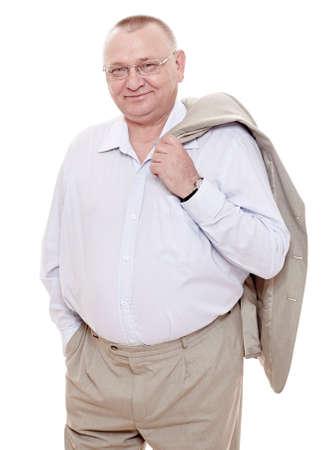 Allegro uomo di mezza età con gli occhiali, camicia con colletto aperto e un vestito beige in piedi con la giacca sulla sua spalla e sorridente isolato su sfondo bianco - felice concetto di pensionamento Archivio Fotografico