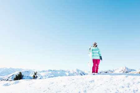 snowboard: Female snowboarder wearing colorful helmet, blue jacket, grey gloves and pink pants standing with snowboard in one hand and looking at beautiful alpine mountain landscape - snowboarding concept
